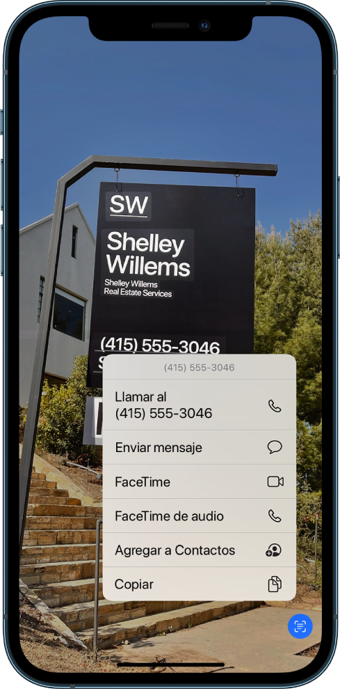Una foto abierta en toda la pantalla. Dentro de la foto hay un letrero que incluye texto y un número telefónico. El número telefónico se selecciona y se muestran las siguientes opciones en pantalla: Llamar, Enviar mensaje, FaceTime, FaceTime de audio, Agregar a Contactos y Copiar.