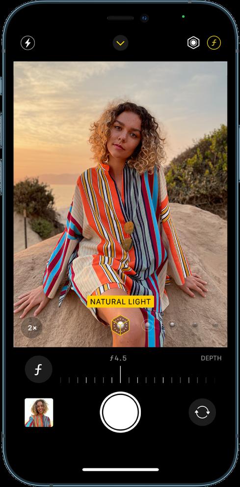 Экран Камеры с режимом «Портрет». Нажата кнопка выбора глубины резкости в правом верхнем углу экрана. В видоискателе виден прямоугольник, который показывает, что для портретного освещения выбран вариант «Естественный свет», и есть бегунок для смены режима освещения. Под видоискателем расположен бегунок регулировки глубины.